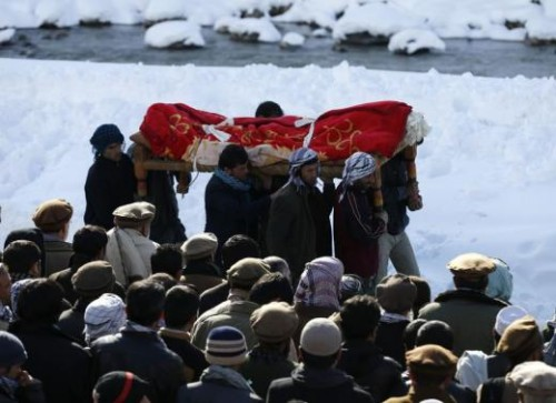 Afghan men carry the body of an avalanche victim for a burial ceremony in Panjshir province, February 26, 2015.