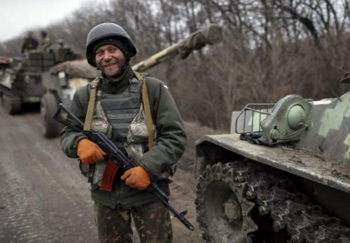 A member of the Ukrainian armed forces and armoured personnel carriers smiles as they prepare to move to pull back from Debaltseve region, near Artemivsk February 26, 2015.
