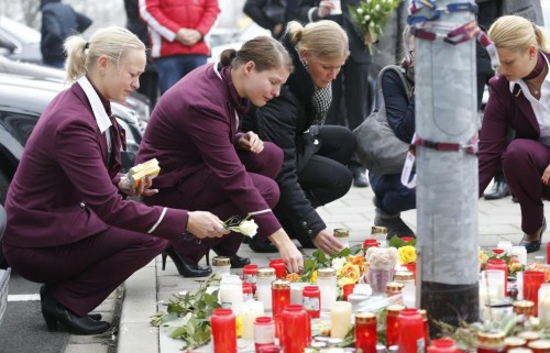 Germanwings employees cry as they place flowers and lit candles outside the company headquarters in Cologne Bonn airport, Germany March 25, 2015.
