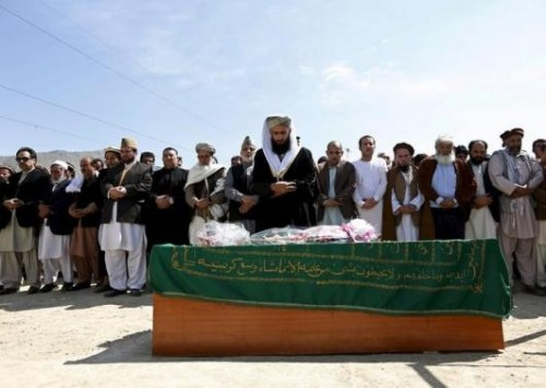 Afghans pray near the coffin of Farkhunda, an Afghan woman who was beaten to death and set alight on fire on Thursday, before her burial ceremony in Kabul March 22, 2015.