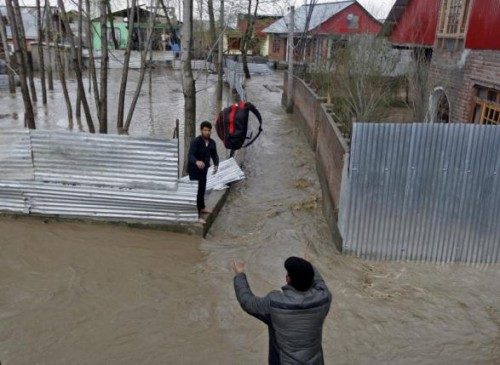 A man throws his belongings towards another to be moved to a safer place at a flooded neighbourhood after incessant rains in Srinagar March 30, 2015. REUTERS