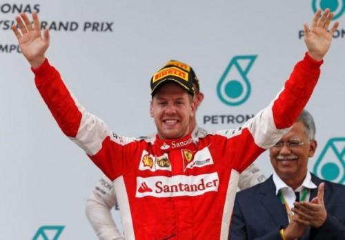 Ferrari's Sebastian Vettel celebrates winning the Malaysian Grand Prix on the podium. Reuters