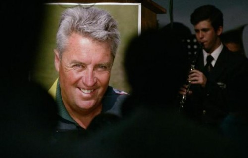 A school boy plays a musical instrument beside a poster of Pakistan cricket coach Bob Woolmer during his memorial service in Cape Town April 4, 2007.