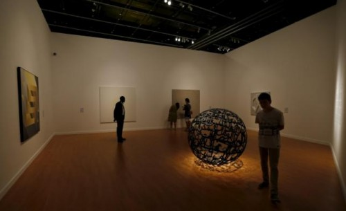 Tourists look at artwork from the Seeing Through Light selections from the Guggenheim Abu Dhabi collection at the Manarat Al Saadiyat Gallery in Abu Dhabi November 27, 2014. Reuters