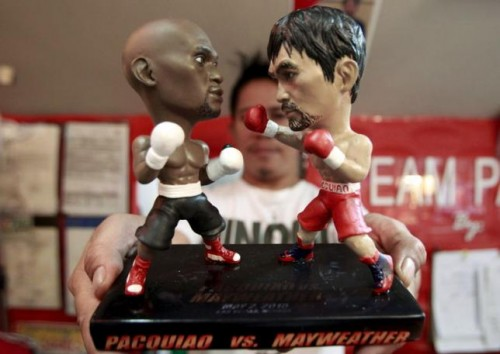 A store employee holds up a stand with miniature figurines of boxers Manny Pacquiao (R) of the Philippines and Floyd Mayweather Jr. of the US, at a mall in Manila April 23, 2015.