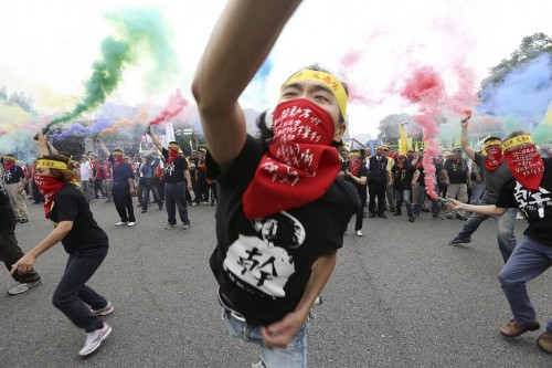 People throw smoke grenades during the annual Labour Day protest in front of Presidential Office in Taipei, Taiwan, May 1, 2015. REUTERS