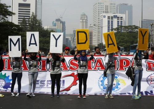 People hold placards during a May Day rally in Jakarta, Indonesia, May 1, 2015. REUTERS