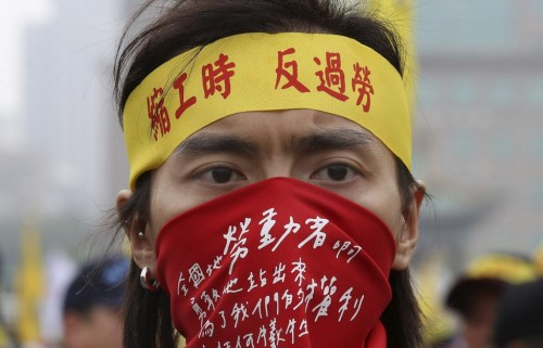 "A demonstrator takes part in the annual Labour Day protest in front of Presidential Office in Taipei, Taiwan, May 1, 2015. His headband reads, ""shorten working hours; no overfatigue."" REUTERS"