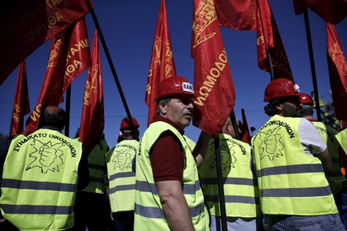 "Protesters from the Communist-affiliated trade union PAME hold red flags during a May Day rally in Athens, Greece May 1, 2015. The words on the vest read: ""Construction workers syndicate"". REUTERS"