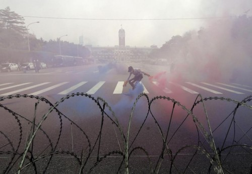 A police officer picks up smoke grenades during the annual Labour Day protest in front of Presidential Office in Taipei, Taiwan, May 1, 2015. REUTERS