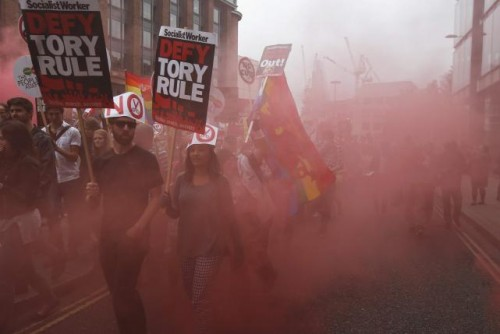 Demonstrators march through red smoke during an anti-austerity protest in central London