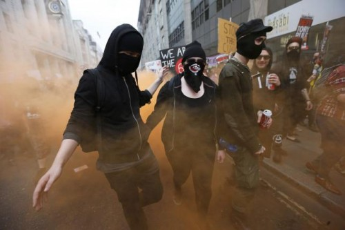 Demonstrators cover their faces as they march during an anti-austerity protest in central London
