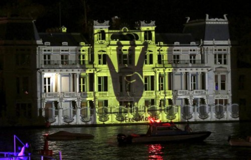 The Rabia sign is projected on the Egyptian Consulate during a protest against an Egyptian court's decision to sentence deposed President Mohamed Mursi to death, in Istanbul