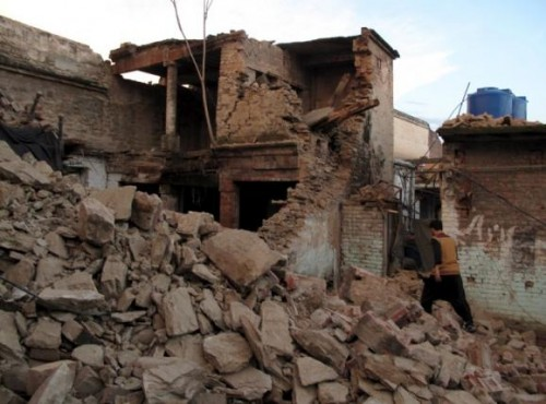 A resident walks past the rubble of a house after it was damaged by an earthquake in Mingora, Swat