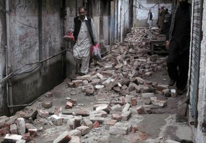 A man with his belongings walks past the rubble of a house after it was damaged by an earthquake in Mingora
