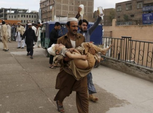 A man carries a boy, who was injured in an earthquake, at the Lady Reading hospital in Peshawar