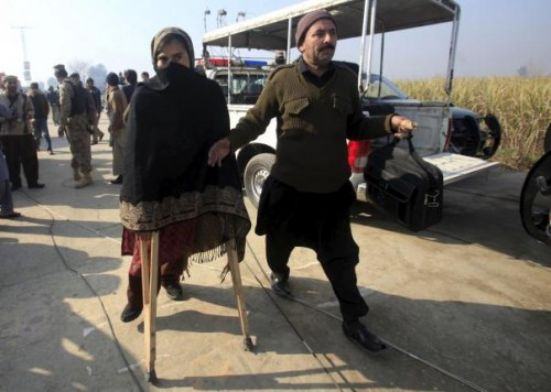 A teacher (L) walks with a pair of crutches following her rescue after a group of militants stormed the Bacha Khan University in Charsadda, Pakistan, January 20, 2016. REUTERS/Fayaz Aziz