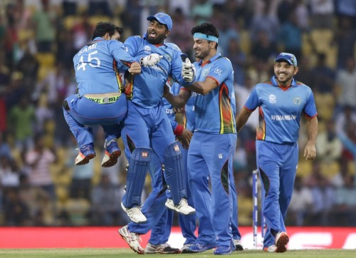 Afghanistan's Samiullah Shenwari, left, celebrates with Mohammad Shahzad, second from left, the run-out of West Indies' batsman Andre Russell during their ICC World Twenty20 2016 cricket match in Nagpur, India, Sunday, March 27, 2016. (AP Photo/Saurabh Das)
