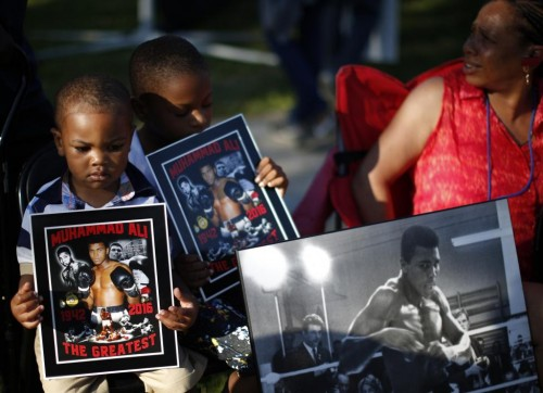 Brandon Liggons, 2, (L) holds an image of Muhammad Ali during the funeral procession for the three-time heavyweight boxing champion in Louisville, Kentucky, U.S., June 10, 2016. REUTERS/Lucy Nicholson