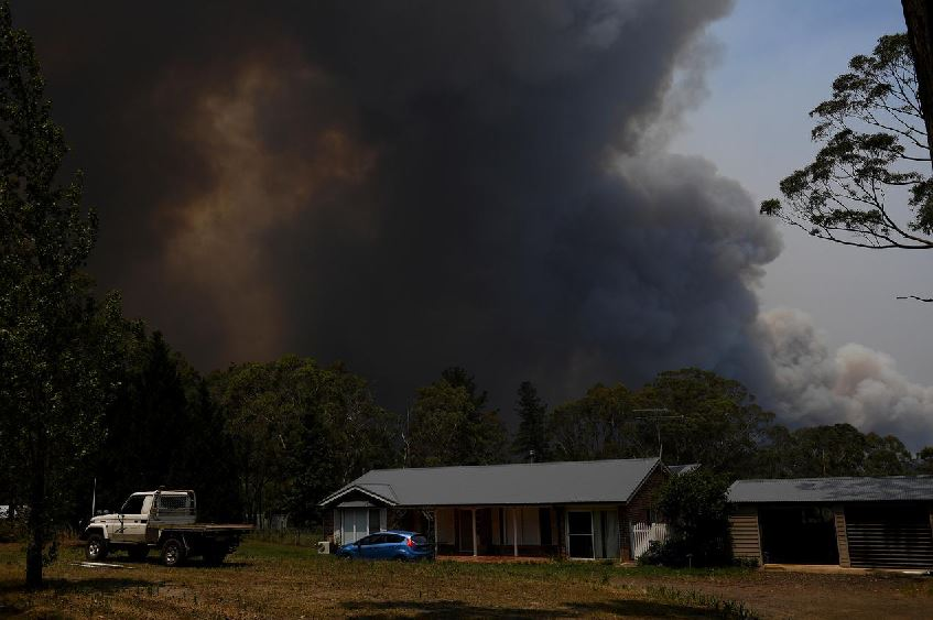 Australian firefighters access badly burned towns, PM defends climate policies