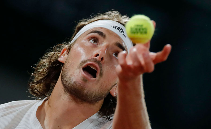 Steely Tsitsipas keeps cool to beat Isner in four sets